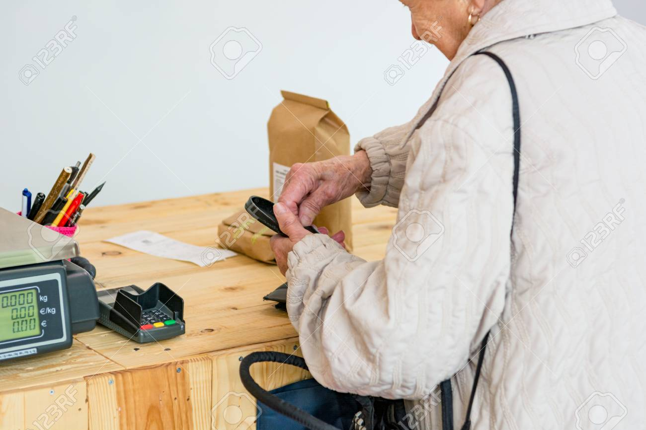 elderly-lady-paying-for-some-organic-products-at-the-counter-of-store